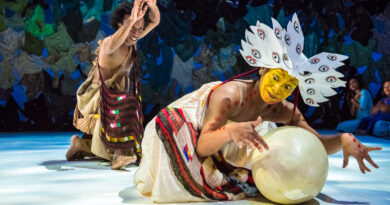 "Indonesian Dancer Rianto performs in a stylised costume representing a bird with bright yellow face paint and protects a large egg. In the background the ""The man who saves the world"" can be seen with a bag slung across his chest and arms above head."
