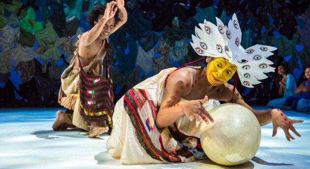 """Indonesian Dancer Rianto performs in a stylised costume representing a bird with bright yellow face paint and protects a large egg. In the background the """"The man who saves the world"""" can be seen with a bag slung across his chest and arms above head."""