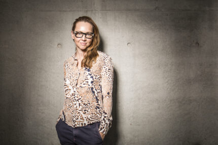 Danielle (with blonde hair and glasses) stands with her hands in her pockets in front of a concrete wall wearing a pink and black top with a collage of leopard print patterns on it and navy trousers