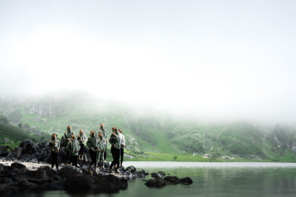 A group of children stand on the edge of the rocky shore of a lake, wearing grey hoodies, surrounded by fog. The bottom of a green mountainside is just visible in the background beneath the fog.