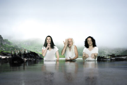 "Pamela Rabe with black hair making a ""shush"" motion with her finger, Olwen Fouéré with white hair and her hand in front of her face splashing water on herself, and Paul Capsis with dark hair reaching towards camera all wear white t-shirts and stand up to their waists in a lake surrounded by fog. To the left a group of children is visible on the rocky bank and in the background the green edge of a mountain is just visible below the fog."